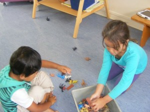 Te Ataakura and Hezekiah co-operate to tidy up the toys quickly.