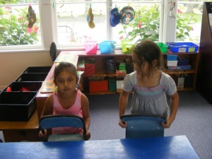 Bonnie-Rose and Kazia are putting the chairs up.